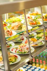 Ausgabevirtrine mit mehreren bunten Salattellern